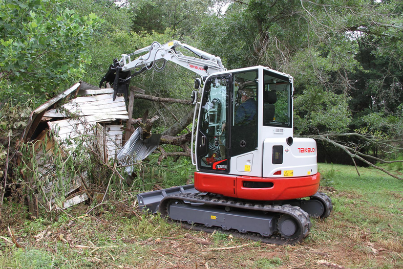 Takeuchi TB257FR compact excavator during demolition on small shed
