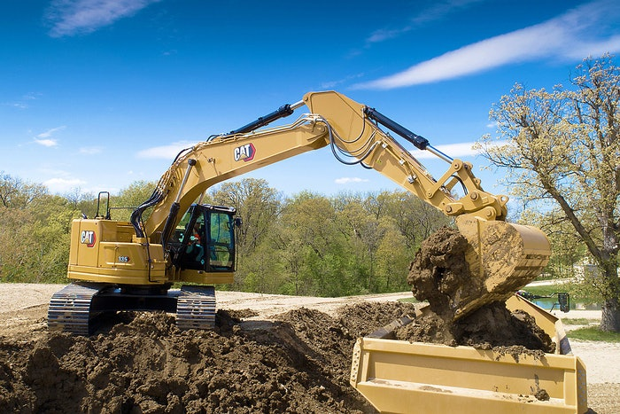 Cat 335 excavator dumping a load of dirt into a dump truck