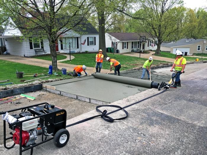 Men using custom drum to pave concrete