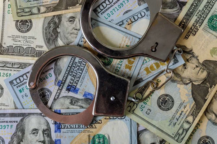 Handcuffs on top of U.S. currency