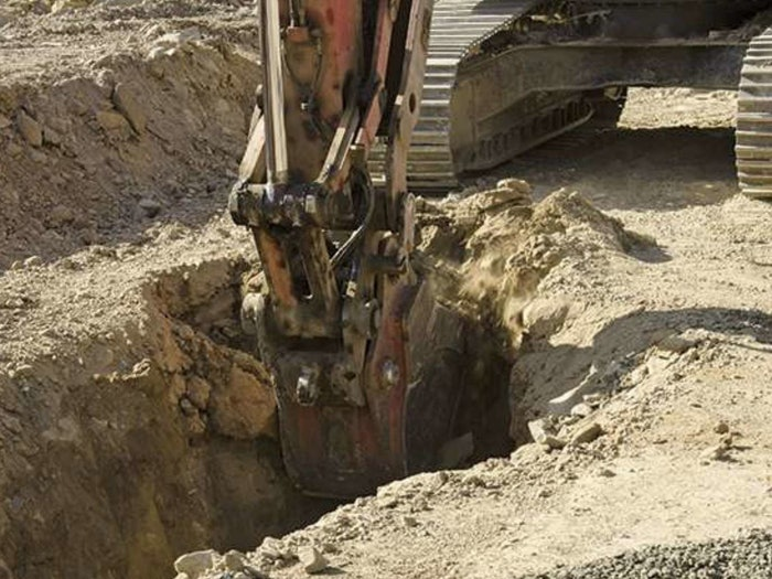 Excavator being used to dig a trench