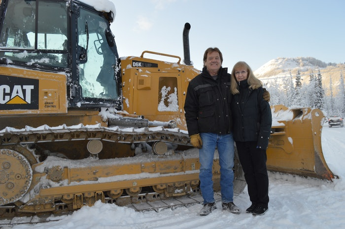 Dirtworks Scott and Dianne Johnson standing in front of a track loader