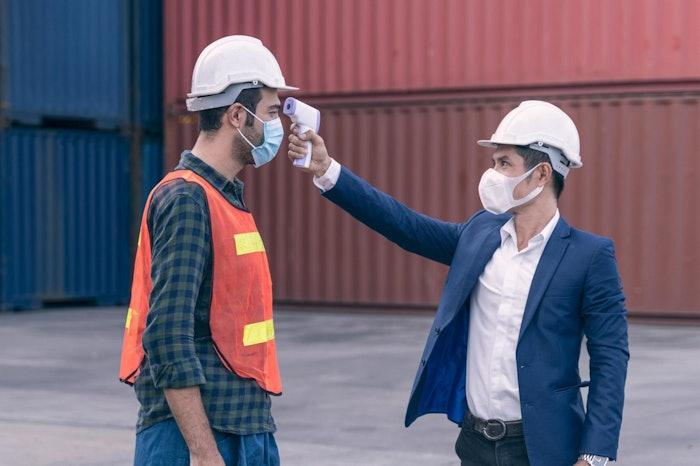 construction worker gets temperature taken at jobsite