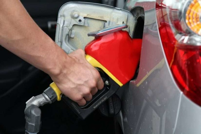 hand pumping gas into vehicle