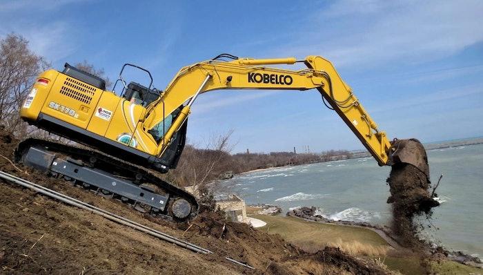 Kobelco SK170LC dumping a bucket of dirt near water