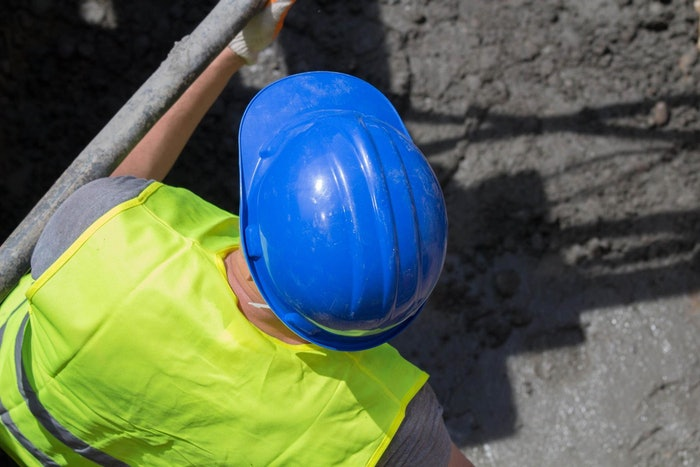 construction worker wearing hard hat and safety vest inside trench