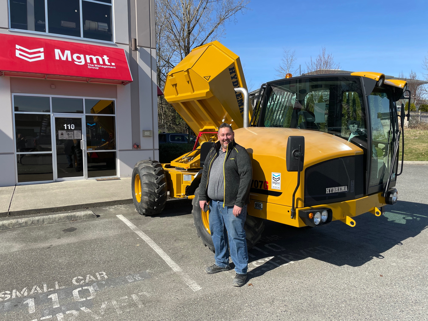 Mike MacKenszie, sales manager of MGMT Group standing beside a Hydrema 707G articulated dump truck