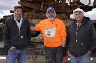 Mike Oberloier wore an orange sweatshirt with his father's picture on the front on the day of the rescue. Here he poses with Thew steam shovel owner Bob Kelly, right, and Kelly's grandson Tommy.