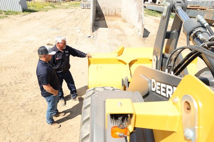 Two men inspecting a piece of John Deere construction equipment