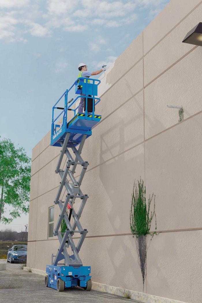Worker painting exterior of building in scissor lift