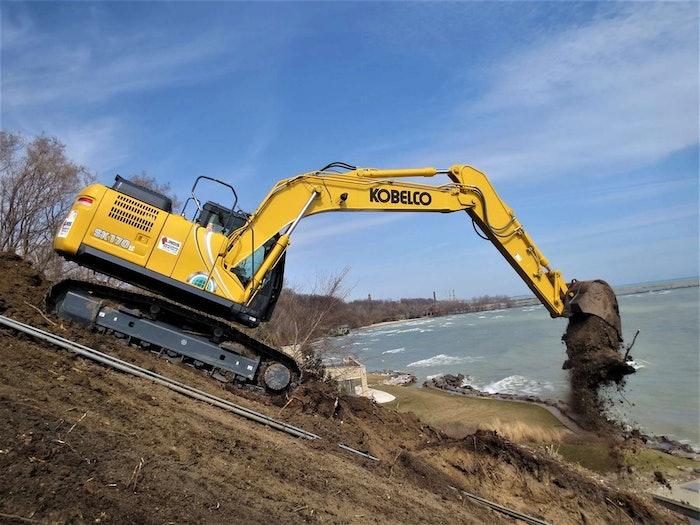 Kobelco excavator dumping dirt next to water