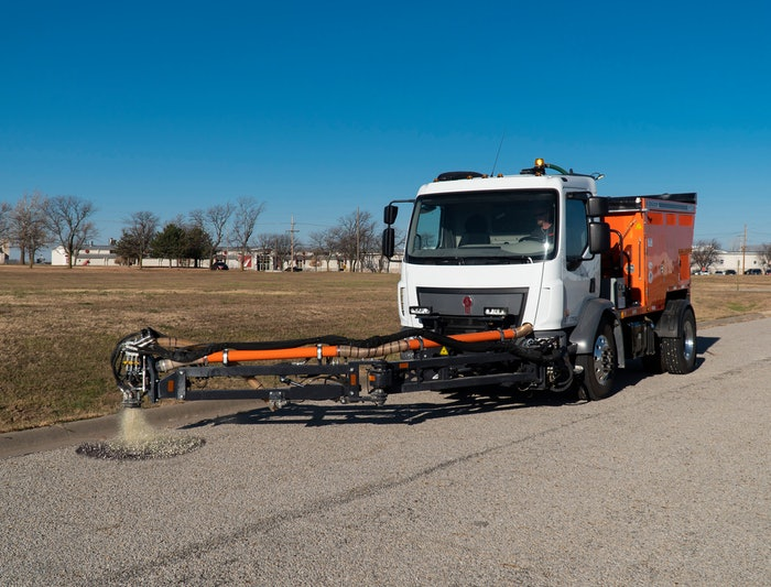 person driving truck with pothole patcher in the process of patching a pothole