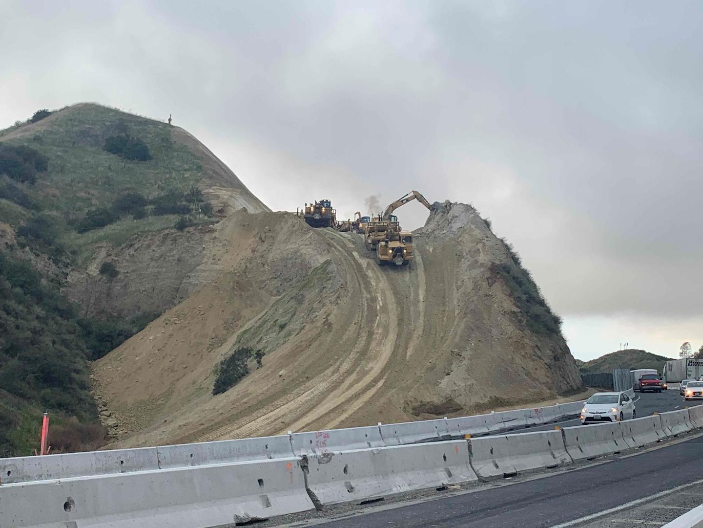 Excavators clearing terrain on side of highway