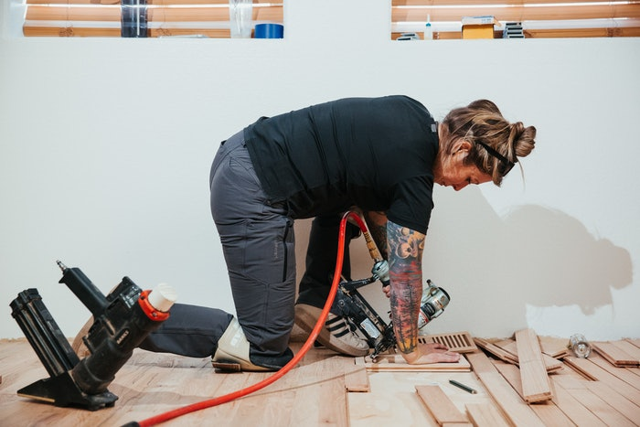 woman laying down wood on floor