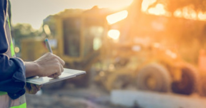 person taking notes on construction job site