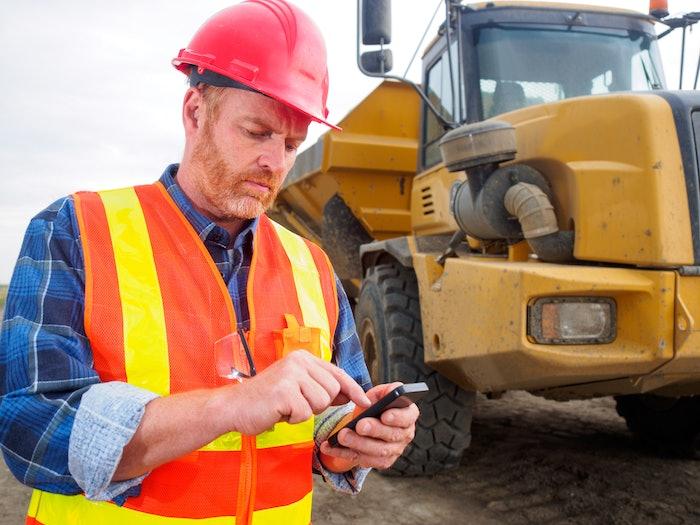 Contractor using phone on jobsite