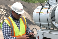 A man wearing a safety vest and hard hat looking at his cell phone