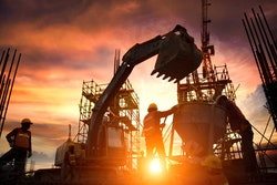 workers wearing safety vests and helmets around an excavator at sunset