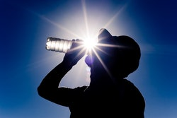 man taking a drink of water from water bottle