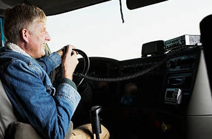 man in drivers seat of truck