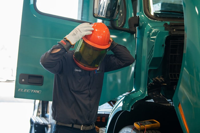 Volvo technician putting on safety helmet with face screen