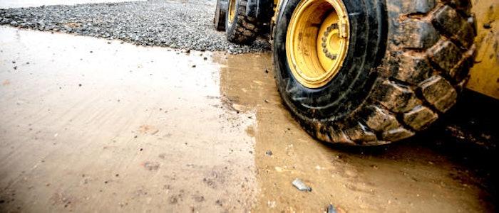 heavy equipment wheel on wet pavement